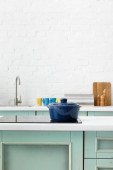 selective focus of white and turquoise kitchen interior with pot on electric induction cooktop