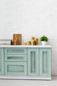 Fotografie moderní bílý a tyrkysový kuchyňský interiér s nádobím, nádobím na jídlo a rostlinou u cihlové zdi