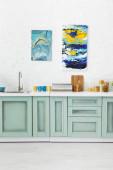 Fotografie moderní bílý a tyrkysový kuchyňský interiér s nádobím a abstraktními obrazy na cihlové zdi