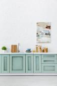 Fotografie bílý a tyrkysový interiér kuchyně s nádobím a abstraktní malbou na cihlové zdi