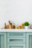 Photo modern white and turquoise kitchen interior with kitchenware, food containers and plant near brick wall