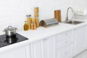 minimalistický moderní bílý kuchyňský interiér s nádobím u cihlové zdi