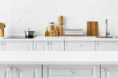 selektivní zaměření prázdného stolu a minimalistický moderní bílý kuchyňský interiér s nádobím a jídlem v blízkosti cihlové zdi na pozadí