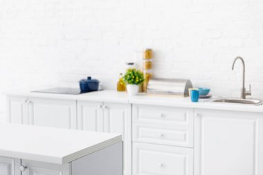 Selective focus of modern white kitchen interior with kitchenware near brick wall stock vector