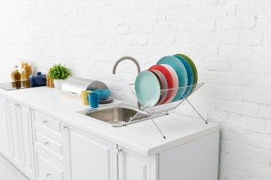 Modern white kitchen interior with kitchenware near brick wall stock vector