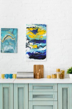 Modern white and turquoise kitchen interior with kitchenware and abstract paintings on brick wall stock vector