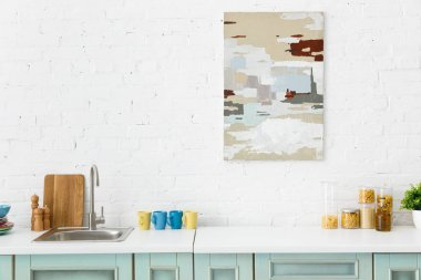 Modern white and turquoise kitchen interior with kitchenware and abstract painting on brick wall stock vector