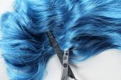 Horní pohled na modré vlasy a nůžky na bílém pozadí