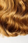 Horní pohled na vlnité hnědé vlasy izolované na bílé