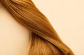 Horní pohled na zkroucené hnědé vlasy na béžovém pozadí