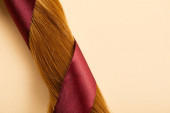 Top view of burgundy ribbon on brown hair on beige background