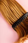 Draufsicht auf braune Haare und Kamm auf rosa Hintergrund