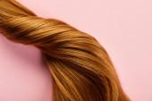 Horní pohled na zkroucené hnědé vlasy na růžovém pozadí