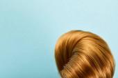 Közelkép a csavart barna haj kék háttér másolási hely