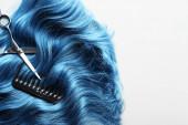 Schere und Kamm auf welligem blauem Haar isoliert auf weißem Grund