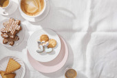 Top view of delicious cookies with coffee on white cloth with copy space
