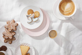 Top view of cookies with glaze and cups of coffee on white tablecloth
