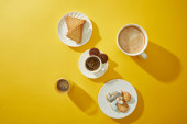 Top view of coffee with delicious cookies on yellow background