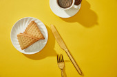 Top view of cup of coffee with golden cutlery and delicious cookies on yellow surface