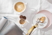 Top view of gourmet cookies with cups of coffee and magazines on white tablecloth
