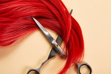 Top view of red hair and scissors on beige background stock vector