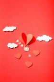 Fotografie horní pohled na papírové srdce ve tvaru vzduchový balón v mracích na červeném pozadí