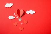 horní pohled na papírové srdce ve tvaru vzduchový balón v mracích na červeném pozadí