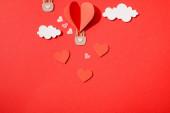 Draufsicht auf Papier herzförmigen Luftballon in Wolken auf rotem Hintergrund