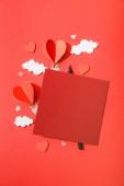 horní pohled na papírové srdce ve tvaru vzduchové balónky v mracích v blízkosti prázdné karty a tužka na červeném pozadí