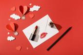 horní pohled na papírové mraky a vzduchové balónky ve tvaru srdce, obálka s otiskem rtu, rtěnkou a tužkou na červeném pozadí