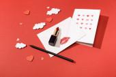 papírové mraky a srdce, blahopřání v blízkosti obálky s otiskem rtu, rtěnkou a tužkou na červeném pozadí