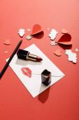 papírové mraky a vzduchové balónky ve tvaru srdce, obálka s otiskem rtu, rtěnka a tužka na červeném pozadí
