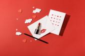 horní pohled na papírové mraky a srdíčka, pohlednice v blízkosti obálky s otiskem rtu, rtěnkou a tužkou na červeném pozadí