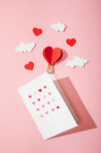 Fotografie top view of greeting card with hearts in white envelope near paper heart shaped air balloon in clouds on pink