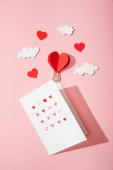 horní pohled na blahopřání se srdcem v bílé obálce v blízkosti papírové srdce ve tvaru vzduchový balón v mracích na růžové