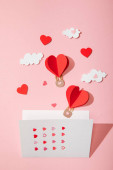 top view of greeting card with hearts near paper heart shaped air balloons in clouds on pink