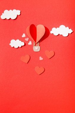 Top view of paper heart shaped air balloon in clouds on red background stock vector
