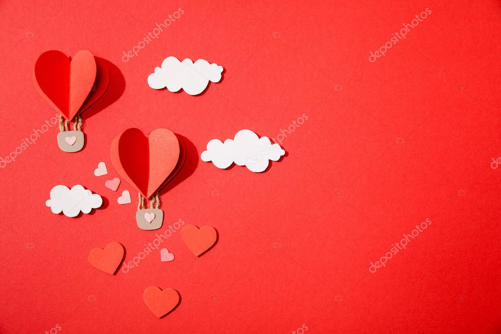 Top view of paper heart shaped air balloons in clouds on red background stock vector