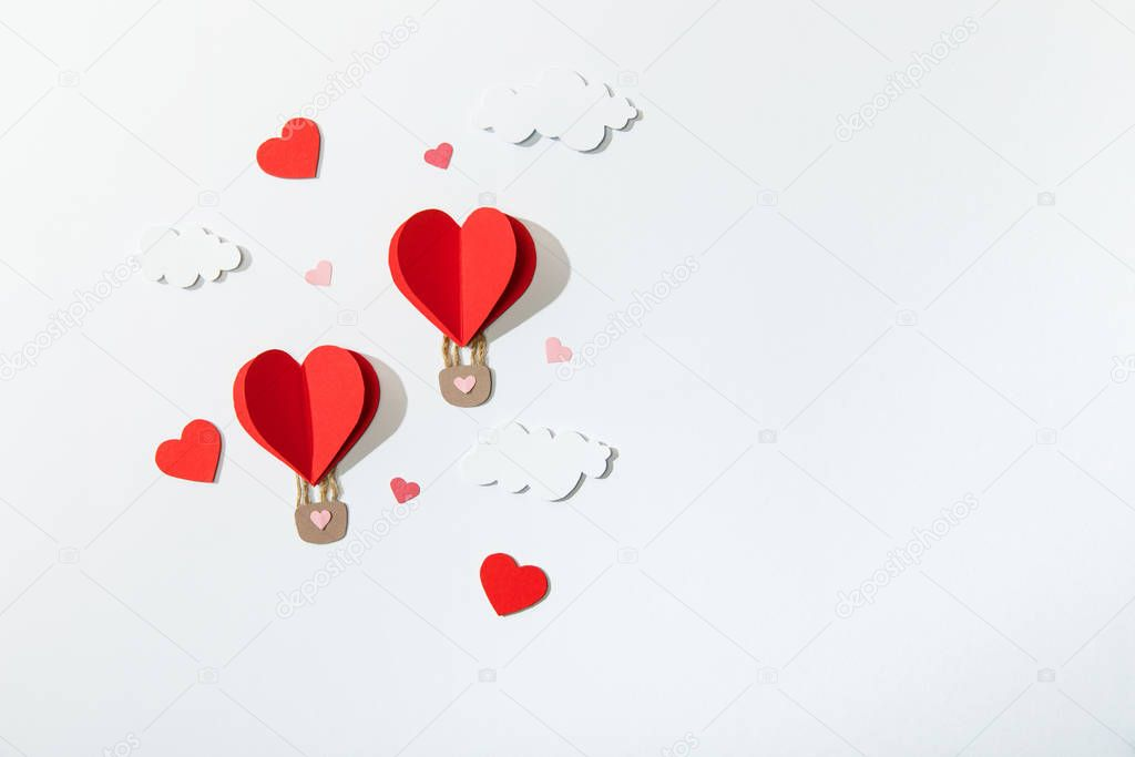 Top view of paper heart shaped air balloons in clouds on white background stock vector