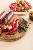 Fotografie delicious meat platters served with olives, spices and breadsticks on plate and wooden board on beige background