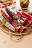 Fotografie vynikající masové mísy podávané s rozmarýnem a chilli paprikou na dřevěné desce na béžovém pozadí