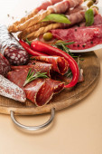 delicious meat platters served with olives, spices and breadsticks on plate and wooden board on beige background