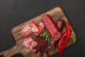 vista dallalto di deliziosi piatti di carne serviti con peperoncino e rosmarino su tavola nera in legno