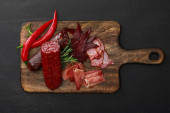 Fotografie top view of delicious meat platter served with chili pepper and rosemary on wooden black table