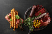 felülnézet ízletes hústálak szolgált olajbogyó, kenyérpálcika és fűszernövények fedélzeten fa fekete asztalon