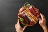 abgeschnittene Ansicht eines Mannes mit köstlicher Fleischplatte, serviert mit Brot und Kräutern an Bord auf einem schwarzen Holztisch