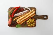 vrchní pohled na lahodný talíř s pečivem, olivami, chilli papričkami a bylinkami na palubě izolované na bílém