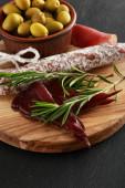 leckere Fleischplatte serviert mit Oliven an Bord auf schwarzer Oberfläche