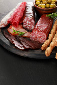 tasty meat platter served with olives and grissini on board on black surface