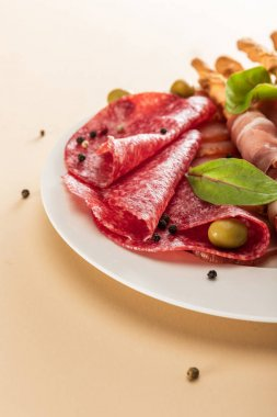 Close up view of delicious meat platter served with olives and breadsticks on plate on beige background stock vector